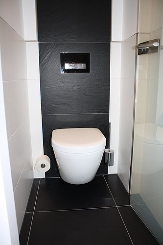 Wall-hung rimless toilet in red toilet room