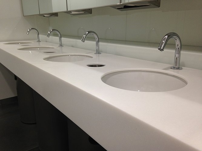 Four undercounter washbasins with touch-free faucets in a public bathroom
