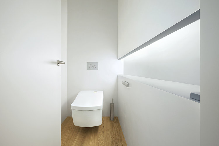 Wall-mounted WASHLET ™ Neorest AC in a white room with a wooden floor