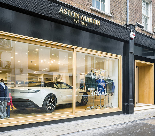 View into a shop window in which a white sports car is presented